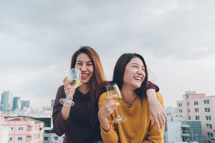 Happy asia girl friends enjoy laughing and cheerful sparkling wine glass at rooftop party,Holiday celebration festive,teeage lifestyle,freedom and fun.lesbian couple
