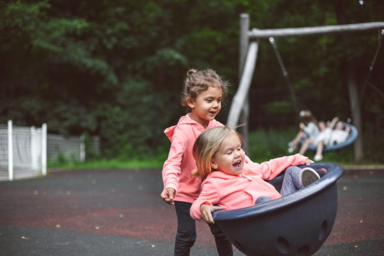 Two cute little girls playing in the playground outside in park. Summer, fun, family and vacations concept. Two sisters having fun.