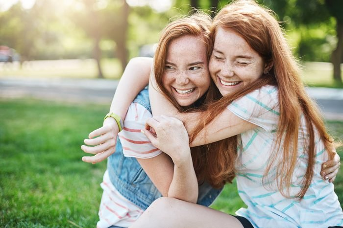 Young girl hugging her older sister smiling. Two red haired ladies having the best time of their lives.