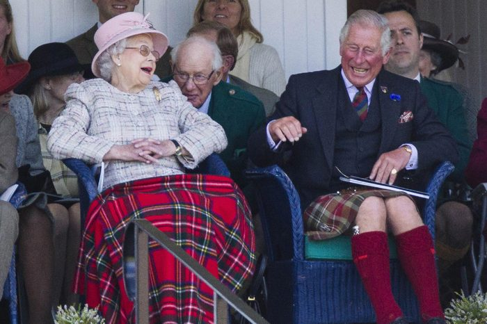 Queen Elizabeth II jokes with Prince Charles during the sack race at the Braemar Gathering.