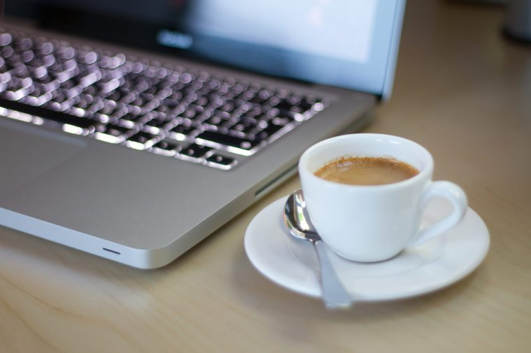 Espresso in a plain white porcelain cup on a desk next to notebook with shallow depth of field.