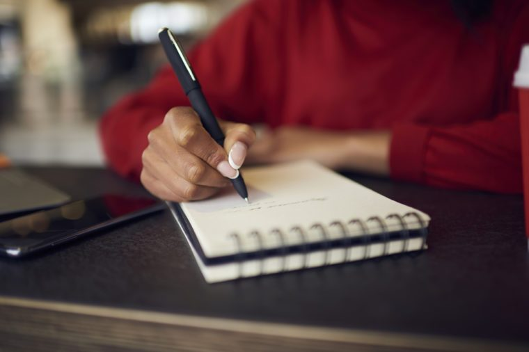 Selective focus on handwriting in spiral notebook creating to do list with targets on white page, cropped image of afro american female designer drawing sketches for project in diary with pen