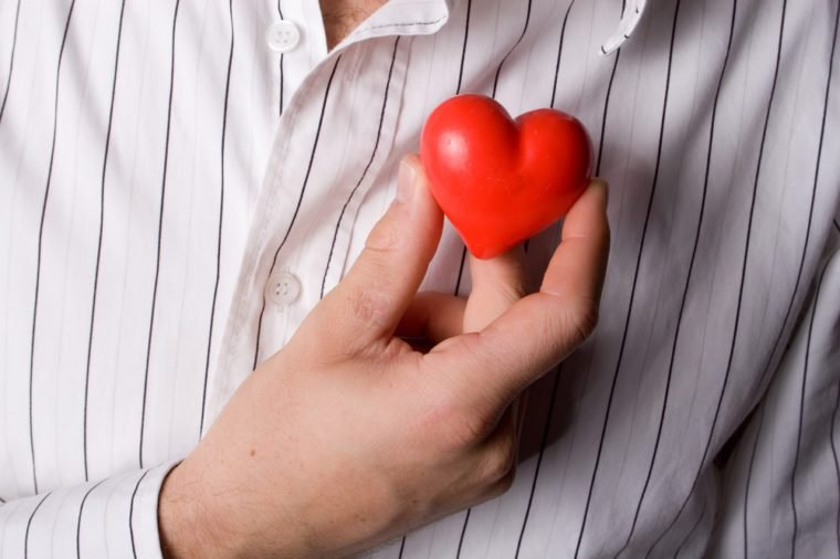A caucasian man holding a small, red heart
