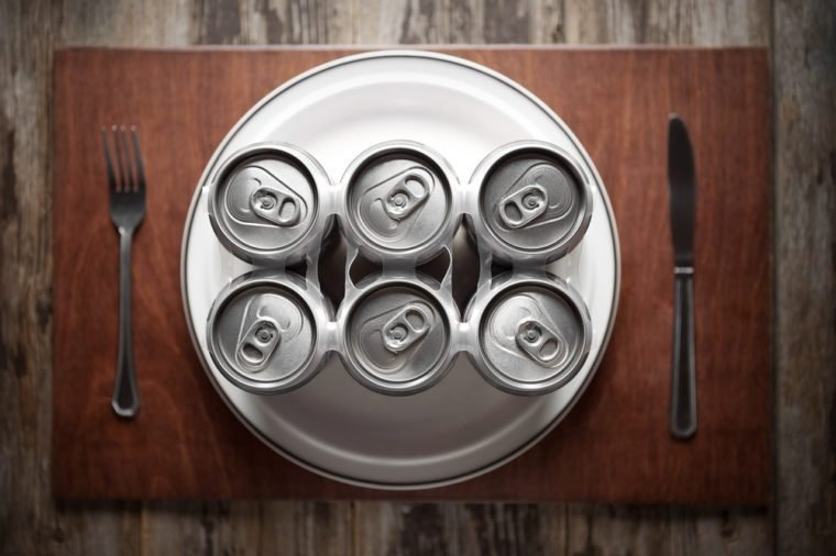 Conceptual image representing alcoholism on a funny way using a six-pack of beer cans for dinner.