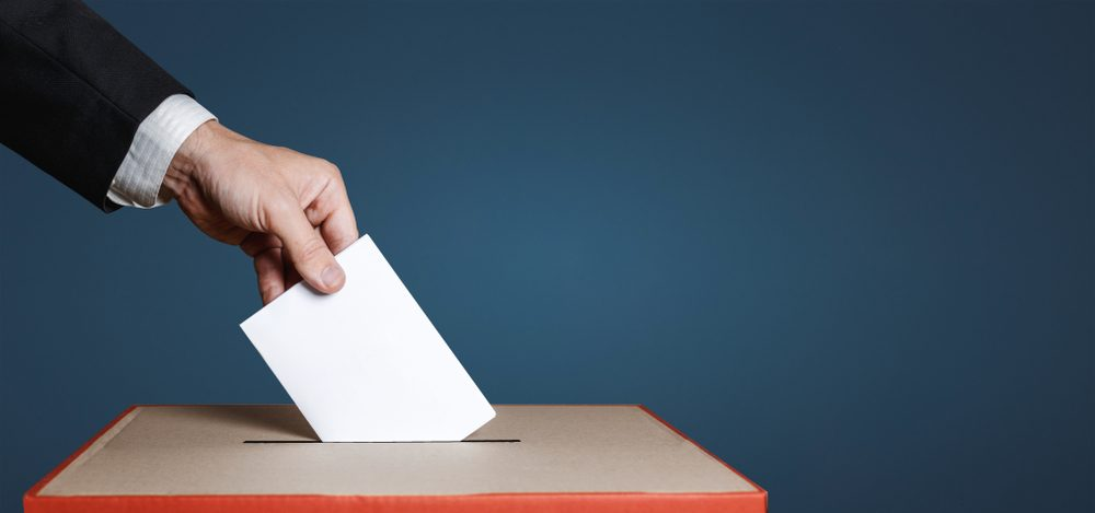Voter Holds Envelope In Hand Above Vote Ballot On Blue Background. Freedom Democracy Concept