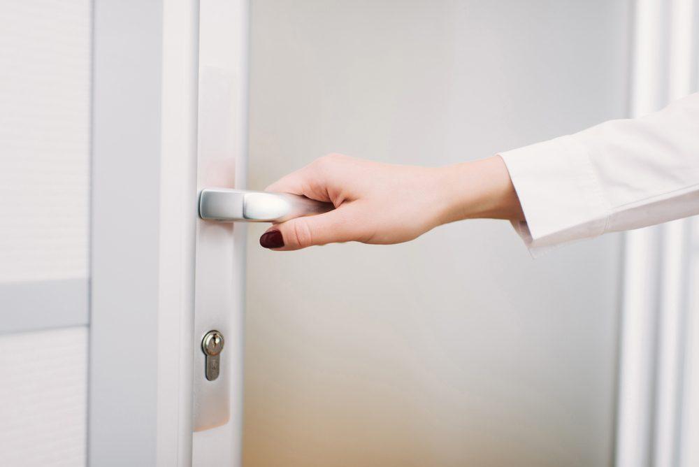 Coming to work, woman's hand opens the door
