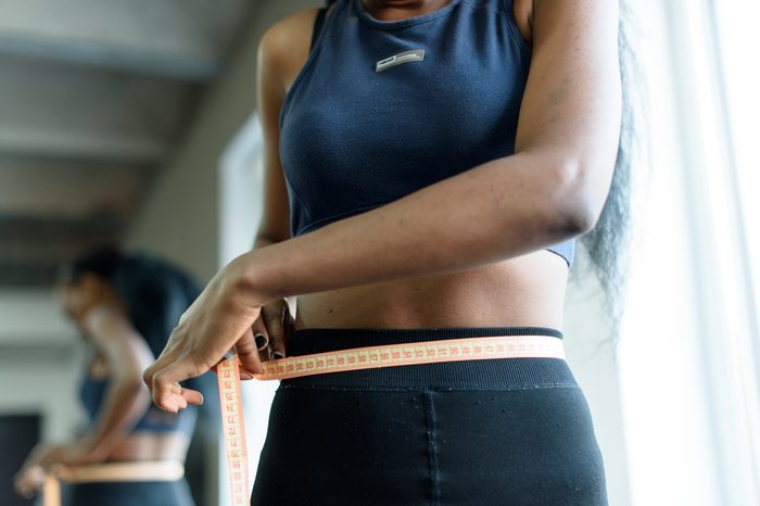 Close-up of young adult black woman in sports clothing. African american girl measuring waist with yellow tape close up