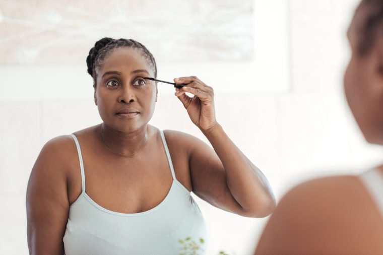 Young African woman standing in her bathroom in the morning applying mascara to her eyelashes in a mirror