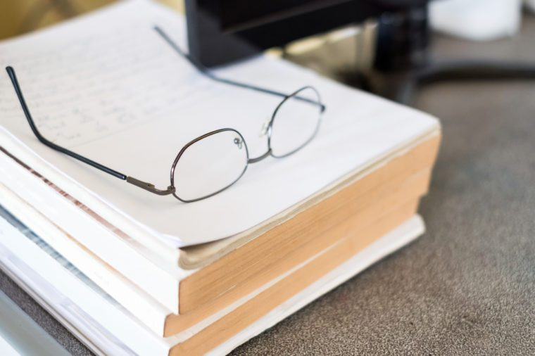 Glasses on pile book with computer on desk