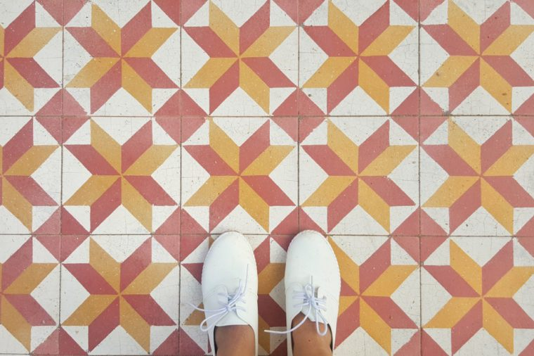 top view of feet selfie on vintage tiles background, white sneakers, copy space