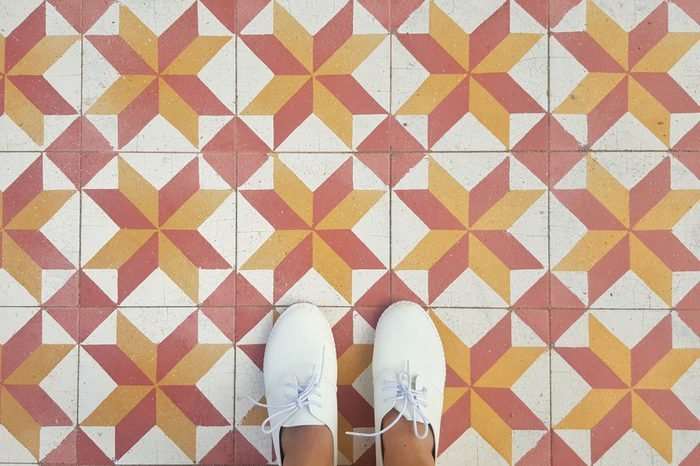 top view of feet selfie on vintage tiles background, white sneakers, copy space