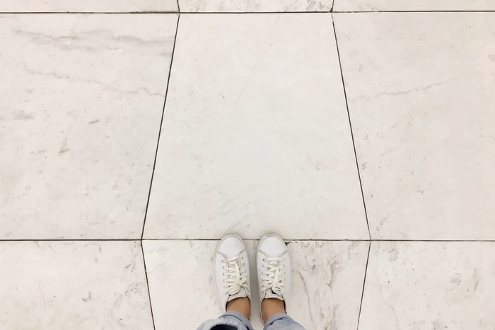 Top view selfie of sneakers shoes on white tiles floor background with copy space
