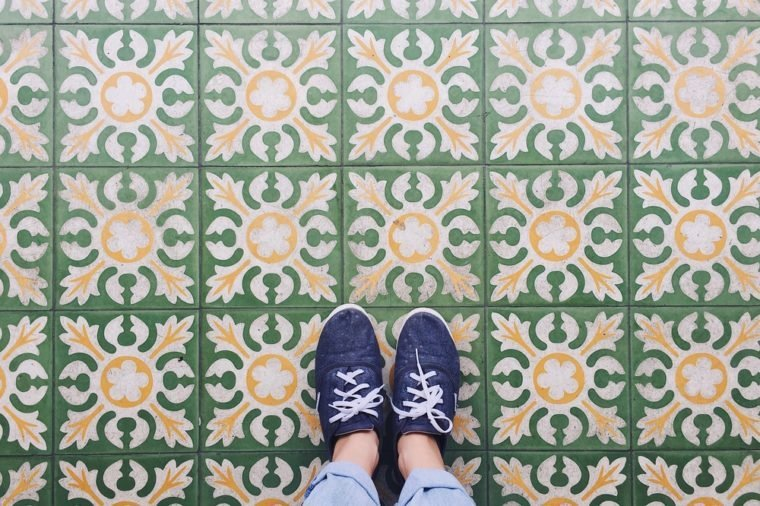Top view selfie of feet in sneaker shoes on vintage art pattern floor with copy space