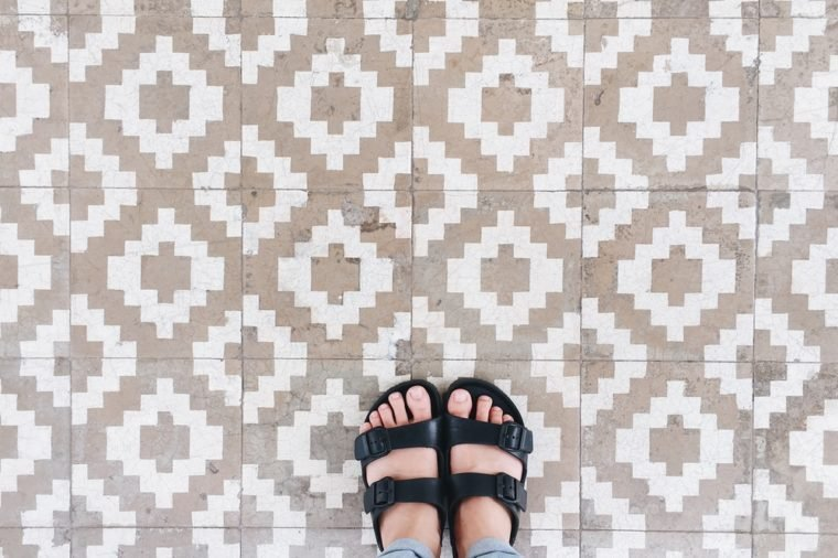 Top view selfie of feet in sandal shoes on vintage tiles floor background with copy space