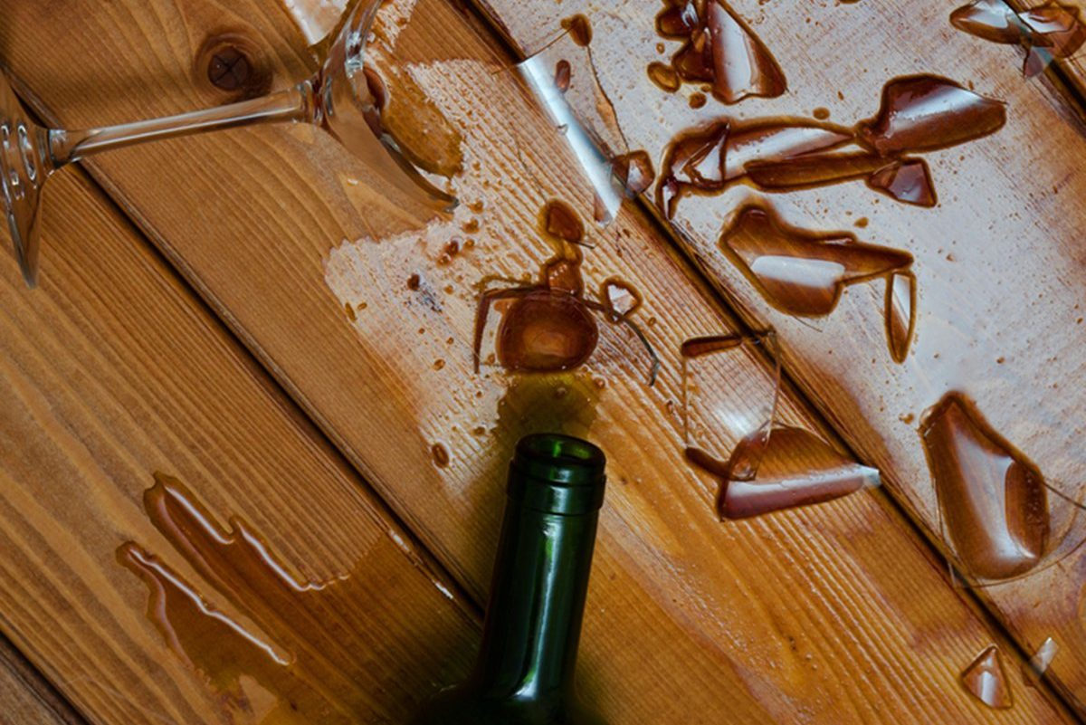broken wine glass with bottle on wooden table
