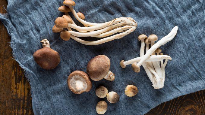 A combination of straw mushroom, tea mushroom, shiitake mushrooms, etc. on a wooden board, gauze for background