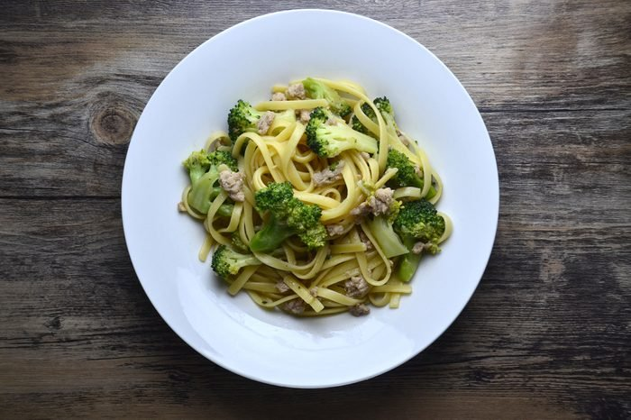 Broccoli spaghetti in white plate on wooden table with top down view