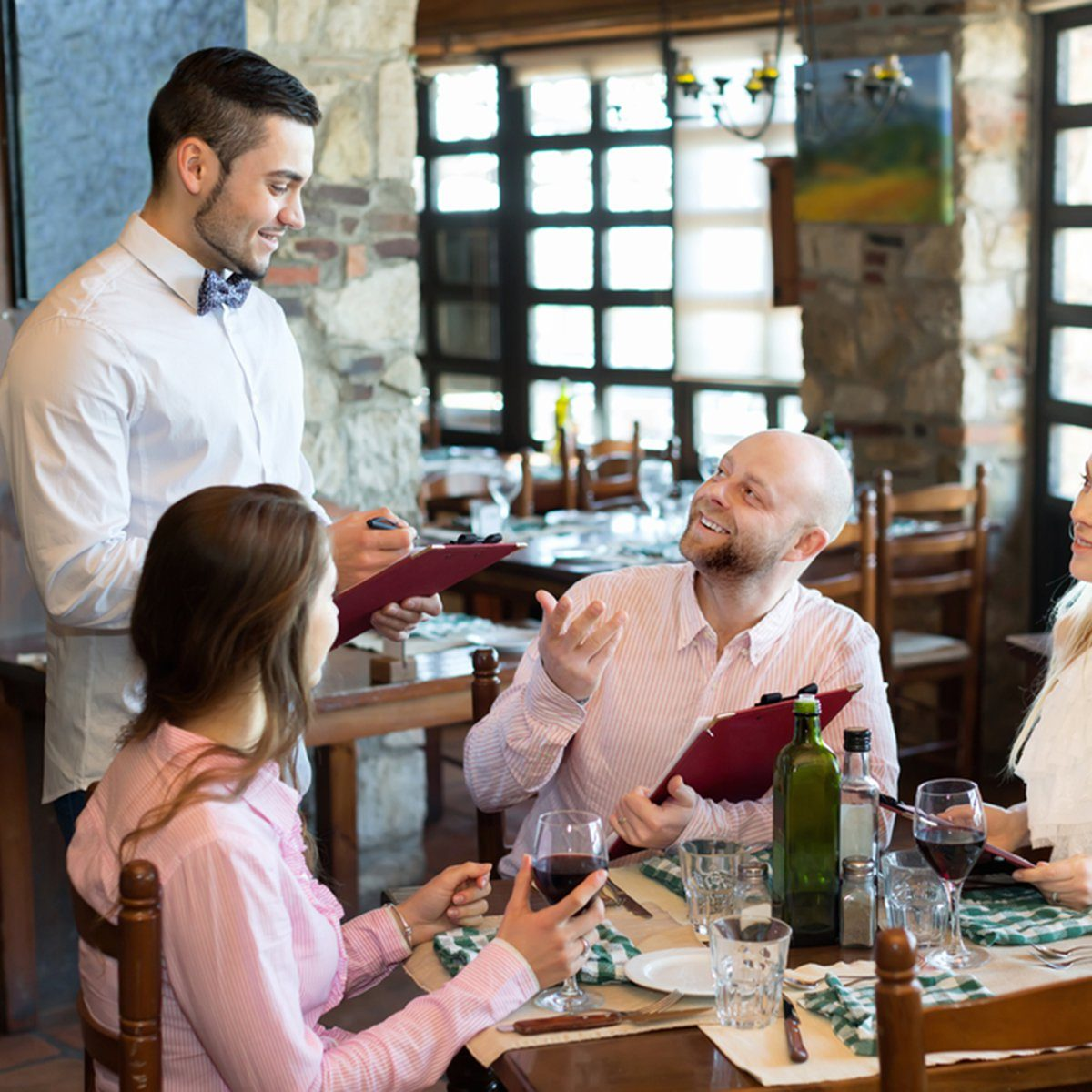 Relaxed adults people having dinner and respectful waiter