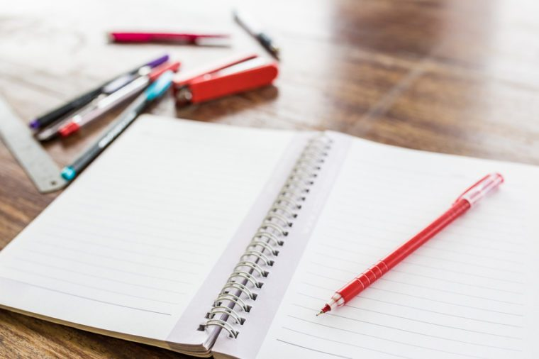 red pen on a blank white notebook with old wooden background,selective focus