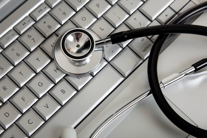 A stethoscope on a computer keyboard on a white background