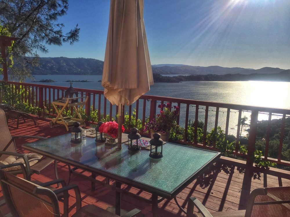 A romantic outdoor patio dining table and chairs with an umbrella overlooks beautiful Clearlake in Lake County California