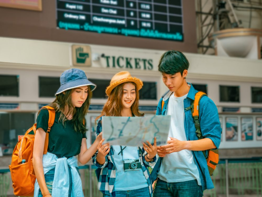 travel concept.group of traveller friend with trikets counter and time table background.asia tourist looking map in terminal at Hualumpong Bangkok train station.