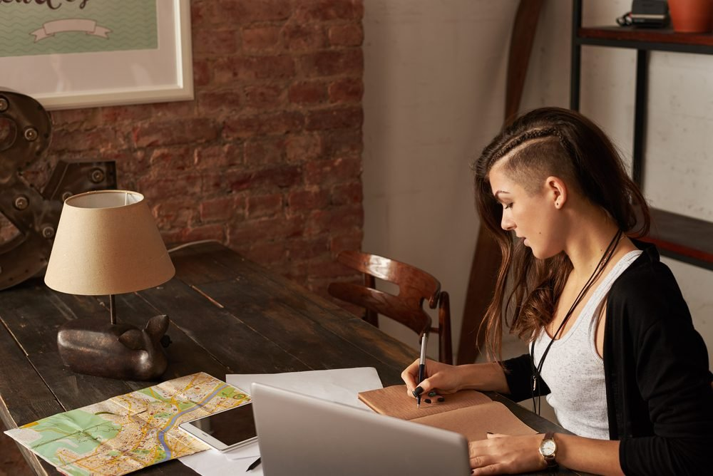 Stylish girl sit at the table in loft room and write. Traveler planning the trip. Handsome latin woman making notes in notepad
