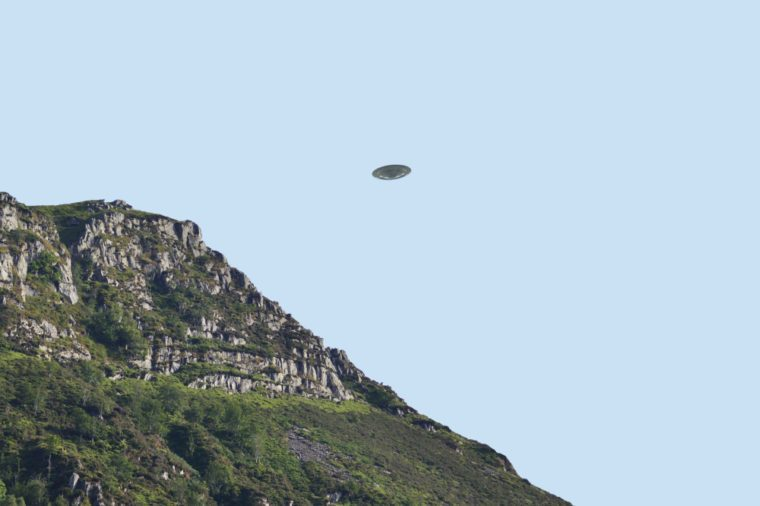 Flying saucer UFO over bluff/ cliff side in summer, clear blue sky background, CGI recreation