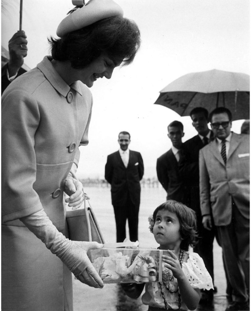 Arrival ceremony at Maiquetia Airport, Caracas, Venezuela. First Lady Jacqueline Kennedy accepts corsage from young Venezuelan.