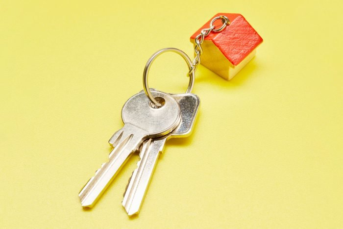 set of keys with house shaped keychain on yellow background