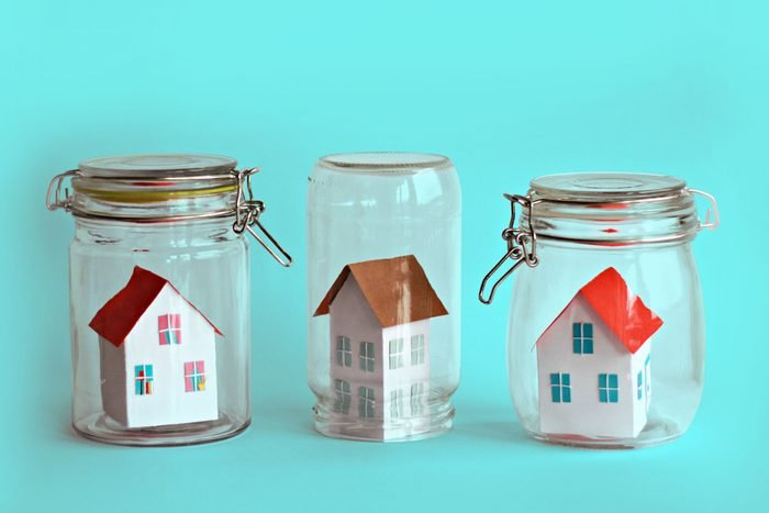 three houses in glass jars on teal background