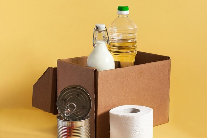 cardboard box with pantry supplies and toilet paper for home on yellow background