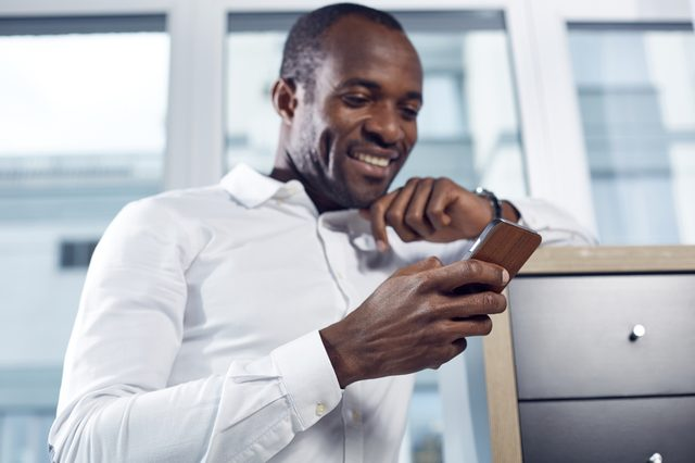 Optimistic news. Selective focus of hand with mobile phone of positive young professional businessman. He is standing in office while leaning elbow on shelf and looking at screen of gadget with smile