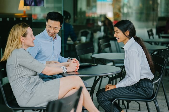 A young Indian Asian woman is interviewing for a job and is speaking with a diverse interview panel in an office in the day. One interviewer is a Chinese man and the other a caucasian man.