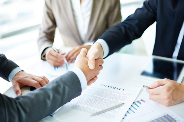 Image of business partners handshaking over business objects on workplace