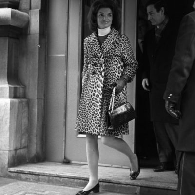 Jackie Kennedy leaving a Manhattan building wearing a leopard skin coat and white turtleneck
