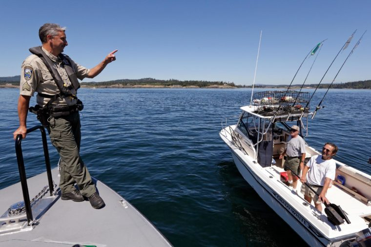 Washington Dept. of Fish and Wildlife Marine Sgt. Russ Mullins, left, talks with fishermen who inadvertently boated too close to passing orca whales in the Salish Sea in the San Juan Islands, Wash. The combination of boats and whales has state and federal authorities worried, especially this year, now that the Southern Resident pod of killer whales has four new calves. By federal and state law, boaters are required to stay 200 yards parallel from the orcas and give them 400 yards in front
