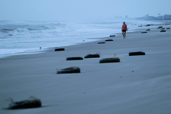 A woman walks on the beach past tires washed up after Hurricane Earl brushed the North Carolina coast in Atlantic Beach, N.C