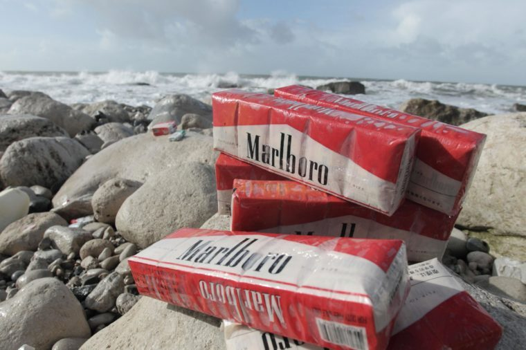 Cigarettes washed up on beach after container spill, Isle of Portland, Dorset, England, February 2014