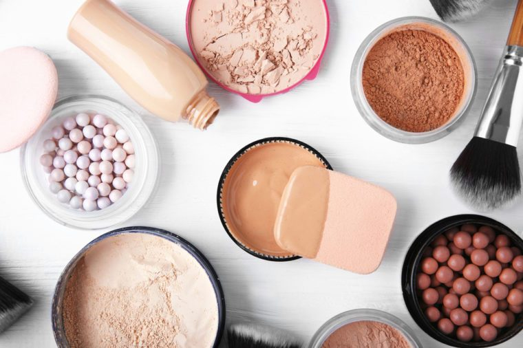 Makeup products and brushes on wooden background