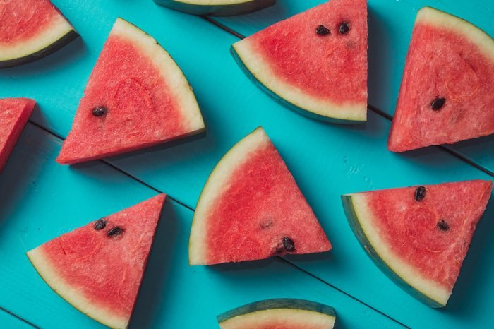 Food or summer concept : Close up patter of many pieces of watermelon laying on blue wooden table with retro color tone.