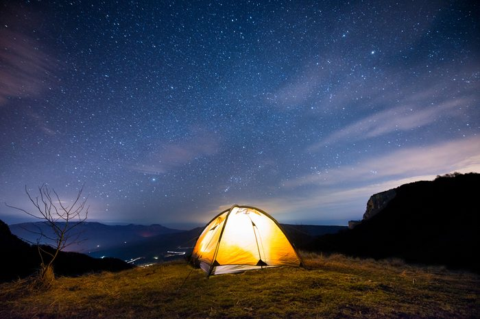 Glowing tent in the mountains under a starry sky