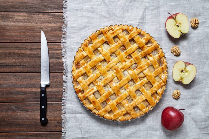 Fresh baked organic classic American apple pie tart with raisins, nuts and cinnamon on a dark wooden background. Top view, rustic style.
