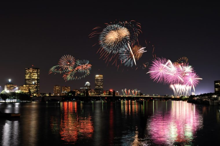 Fireworks over Boston on 4th of July celebration. Light reflections on Charles River, city skyline on background