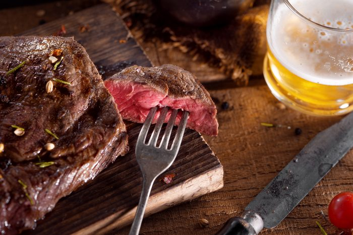 close up view on nice fresh steak on color background