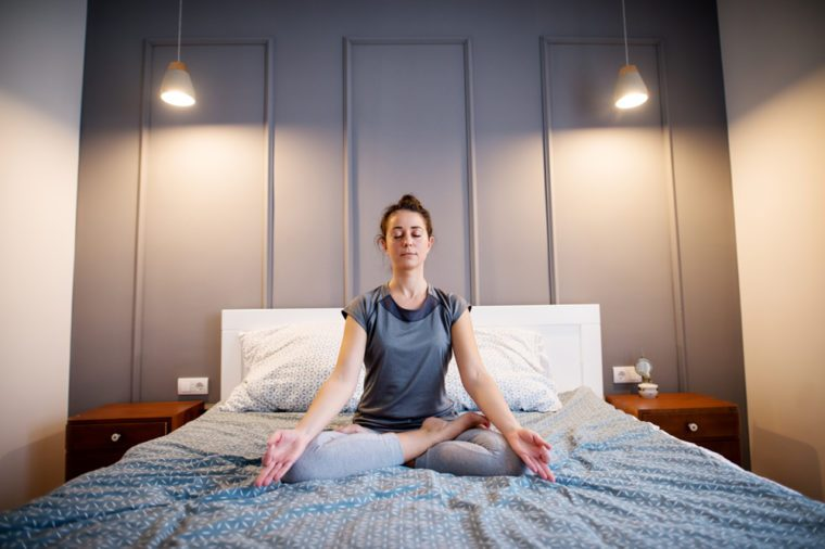 Front view of peaceful attractive middle aged active woman practising yoga on the bed holding eyes closed, sitting in Half Lotus exercise, Ardha Padmasana pose and wearing sportswear in the morning.