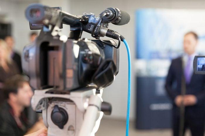 Video camera in focus, blurred spokesman in background