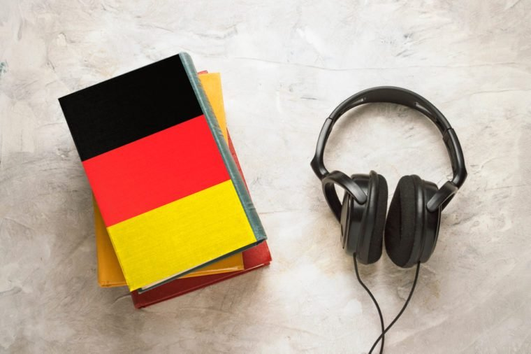 Headphones and a pile of books. The top book has a cover in the form of a flag of Germany. Concept audiobooks. Learning languages. German language.