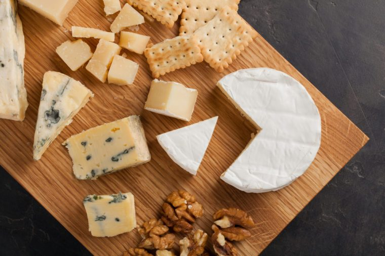Tasting cheese dish on a wooden plate. Food for wine and romantic, cheese delicatessen on a dark stone table. Top view.