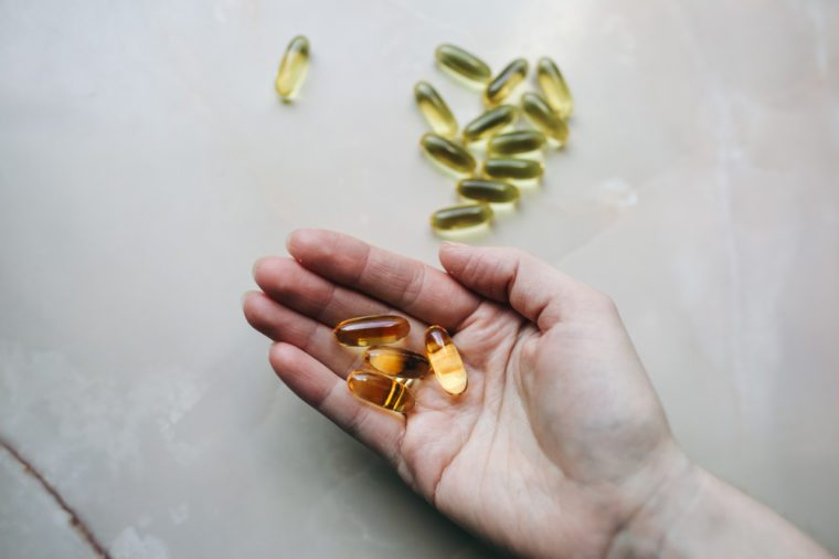 Omega 3 pills in woman's hand on marble background. Healthy diet supplements. Fish oils for vegans food.